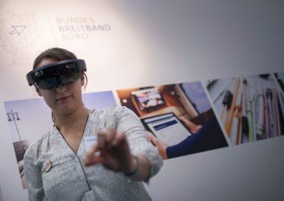 """Katharina Hirt (Team Bildungsmanagement, atene KOM GmbH) mit einer Augmented Reality (AR) Brille am Stand des Breitbandbüros des Bundes am 26.10.2017 in Berlin bei der Messe """"Digitale Regionen - heute und morgen"""". Foto: atene KOM / Florian Schuh"""